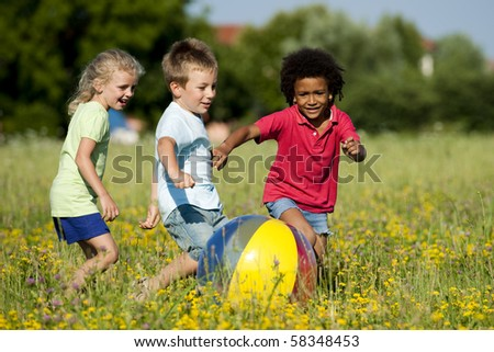 Multi-ethnic children playing ball - stock photo