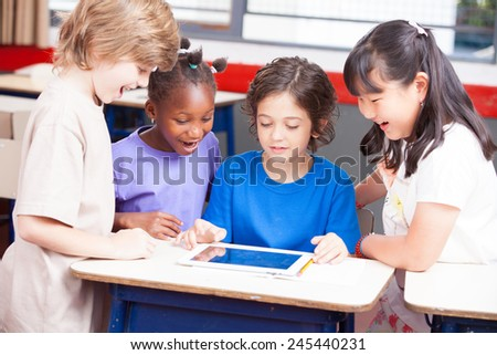 Multi-ethnic classroom playing with tablet. Happy school concept. - stock photo