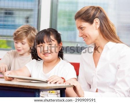 Multi-ethnic classroom. Teacher using tablet with asian student. - stock photo