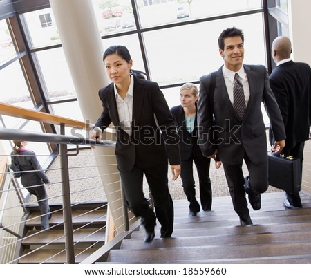 Multi-ethnic co-workers ascending and descending office stairs - stock photo