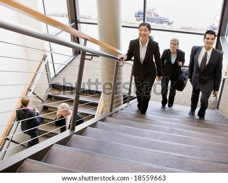 Multi-ethnic co-workers ascending office stairs - stock photo