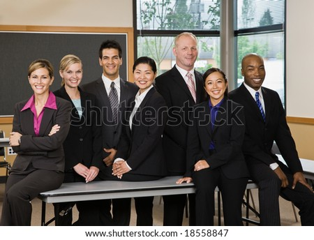 Multi-ethnic co-workers posing in conference room - stock photo
