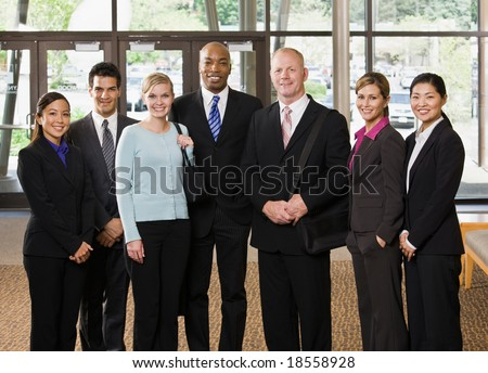 Multi-ethnic co-workers posing in office lobby - stock photo
