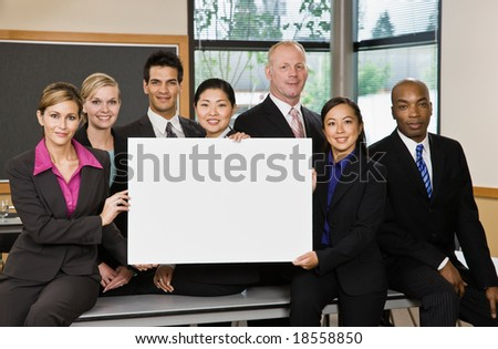 Multi-ethnic co-workers posing with blank sign in conference room - stock photo