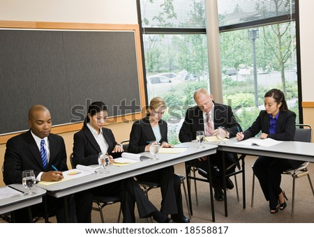 Multi-ethnic co-workers sitting around table in conference room - stock photo