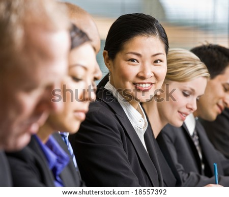 Multi-ethnic co-workers sitting in a row - stock photo