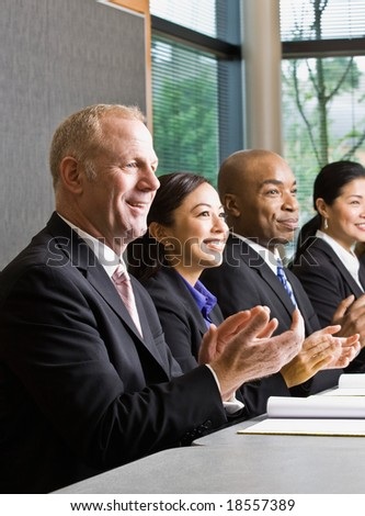 Multi-ethnic co-workers sitting in a row, applauding at conference table - stock photo