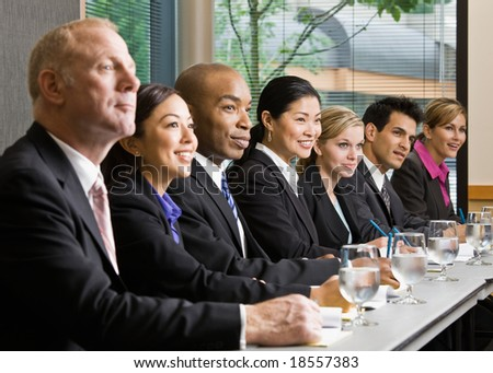 Multi-ethnic co-workers sitting in a row at conference table - stock photo