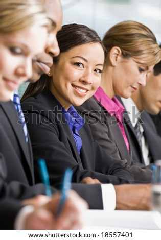 Multi-ethnic co-workers sitting in a row, writing at conference table - stock photo
