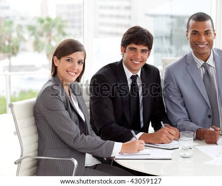 Multi-ethnic co-workers smiling at the camera in a meeting