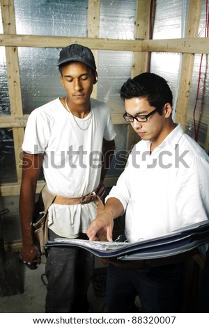 Multi ethnic construction team looking over blue prints inside house