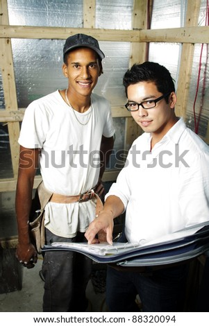 Multi ethnic construction team looking over blue prints inside house smiling - stock photo