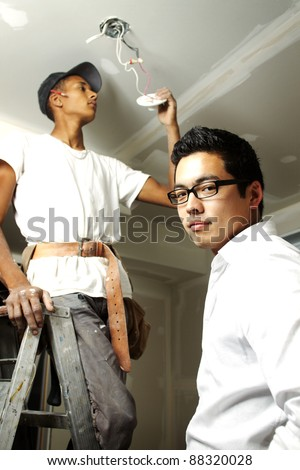 Multi ethnic construction team working on wiring in house - stock photo