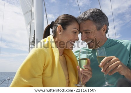 Multi-ethnic couple drinking champagne on sailboat - stock photo