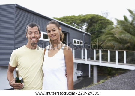 Multi-ethnic couple holding champagne in front of house - stock photo