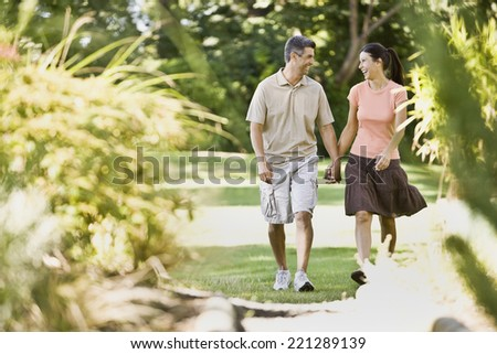 Multi-ethnic couple holding hands - stock photo