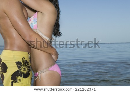 Multi-ethnic couple in bathing suits hugging - stock photo