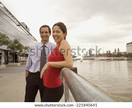 Multi-ethnic couple leaning on railing - stock photo