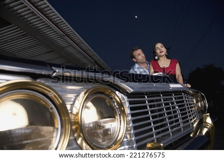 Multi-ethnic couple leaning on show car - stock photo