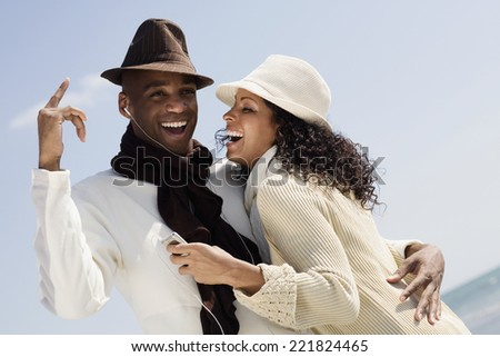 Multi-ethnic couple listening to mp3 same player - stock photo