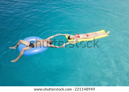 Multi-ethnic couple on floats in water - stock photo