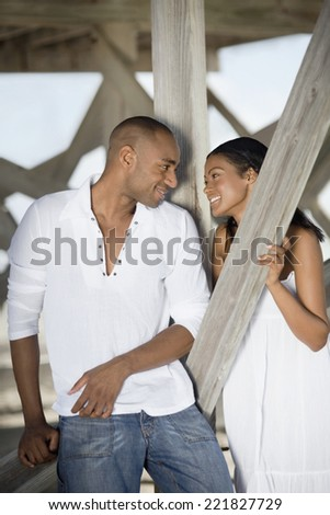 Multi-ethnic couple smiling at each other - stock photo