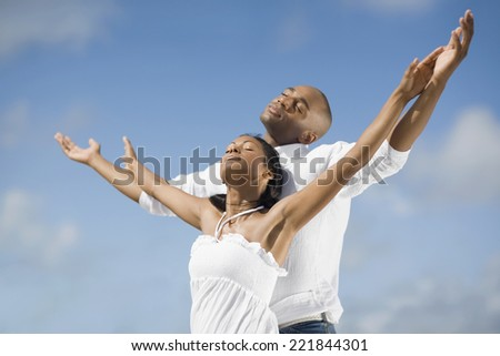 Multi-ethnic couple with arms raised - stock photo