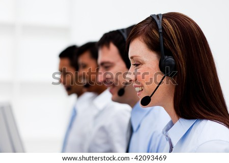 Multi-ethnic customer service agents with headset on in a call center - stock photo