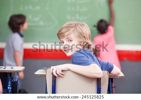 Multi ethnic elementary classroom. Kid looking at camera while classmates at chalkboard.