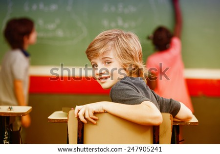 Multi ethnic elementary classroom. Kid looking at camera while classmates at chalkboard. - stock photo