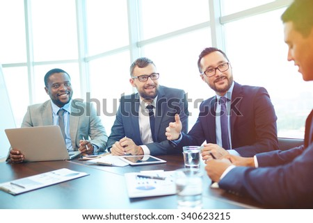Multi-ethnic employees looking at their colleague during discussion at meeting - stock photo