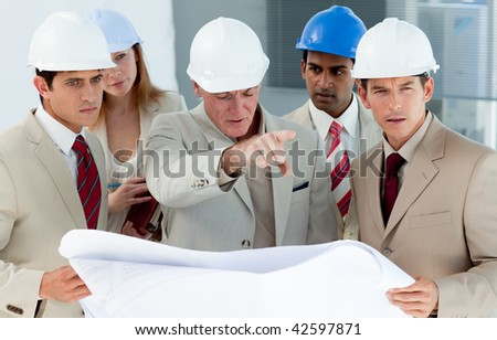 Multi-ethnic engineers studying plans in a building site - stock photo