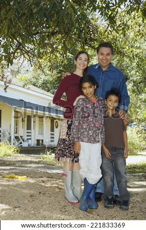 Multi-ethnic family in front of house - stock photo