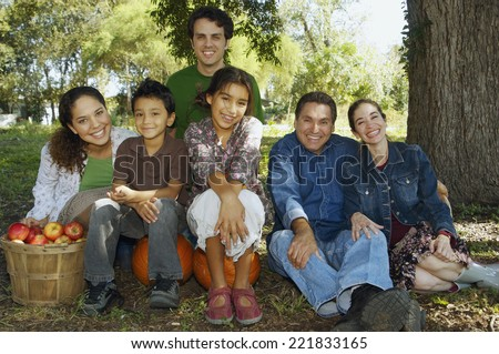 Multi-ethnic family sitting under tree - stock photo