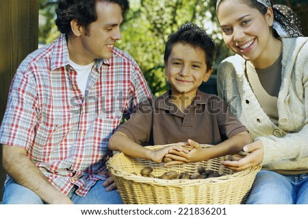 Multi-ethnic family with basket of organic produce - stock photo