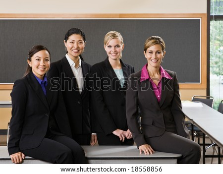 Multi-ethnic female co-workers posing in conference room - stock photo