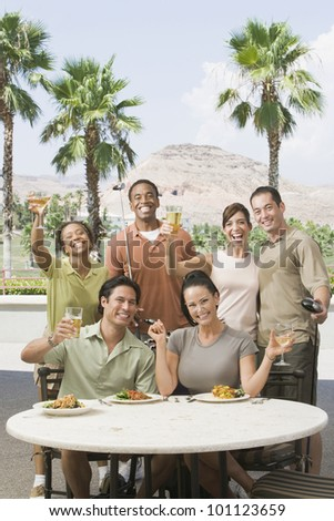 Multi-ethnic friends drinking at golf clubhouse - stock photo