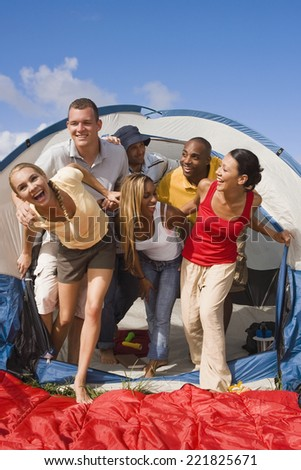Multi-ethnic friends exiting tent - stock photo