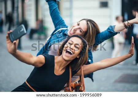 Multi ethnic Friends having fun in city taking selfie - stock photo
