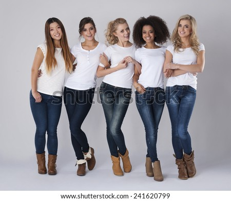 Multi ethnic friends wearing jeans and white t-shirts - stock photo