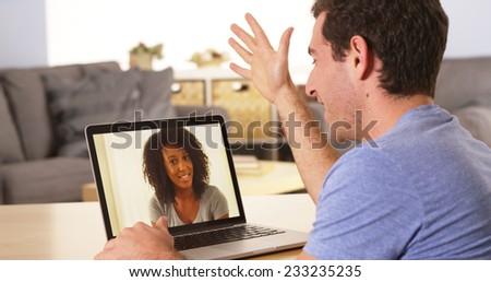 Multi-ethnic friends webcamming on laptop - stock photo