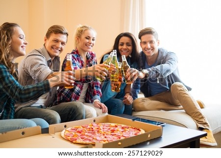 Multi-ethnic friends with pizza and bottles of drinks having party - stock photo