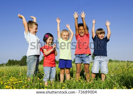 Multi-Ethnic group of children outdoors, arms raised - stock photo