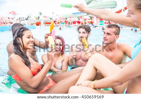 Multi-ethnic group of friends eating ice cream in a swimming pool - Young happy people having fun and enjoying summertime in a aquapark - stock photo