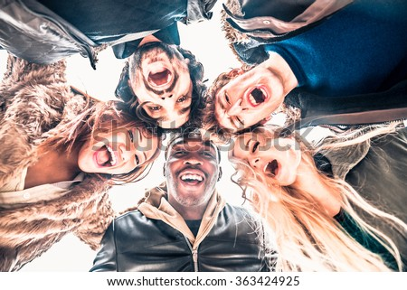 Multi-ethnic group of friends in circle - Several people of diverse ethnics smiling and looking down at camera - Concepts about friendship, teamwork, immigration and unity - stock photo