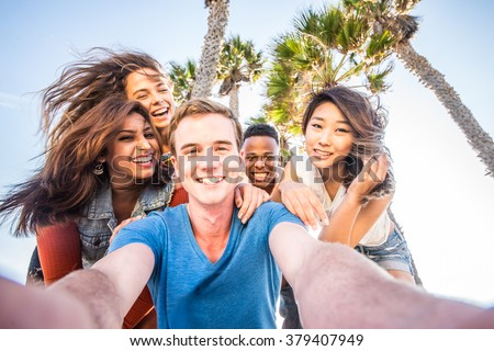 Multi-ethnic group of friends taking a self portrait picture with a camera phone - Cheerful people of diverse ethnics having fun and partying outdoors on a summer vacation - stock photo