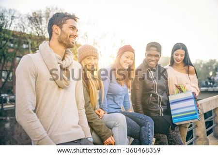 Multi-ethnic group of friends talking and laughing outdoors - Happy students having fun while having a conversation outdoors - stock photo