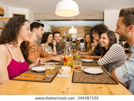 Multi-Ethnic Group of happy friends lunching and having fun at the restaurant - stock photo