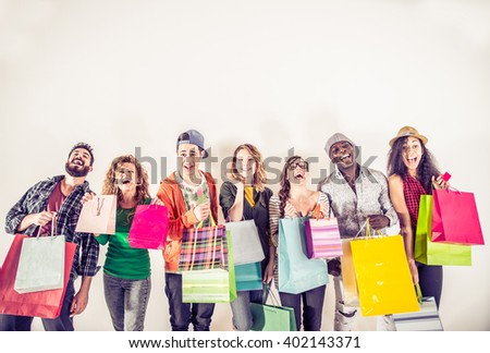 Multi-ethnic group of people holding colored shopping bags and laughing - Portrait of funny friends posing on white background - stock photo