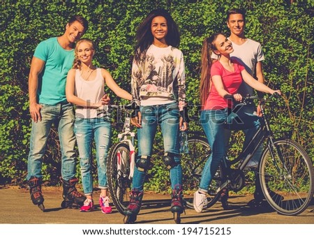 Multi ethnic group of sporty teenage friends in a park  - stock photo